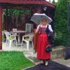 Eine Frau in Tracht mit einem Sonnenschirm